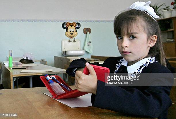 Ossetian pupil prepares for lesson at the school in Beslan North Ossetia 15 September 2004 as schools in the town reopen after the hostage crisis...