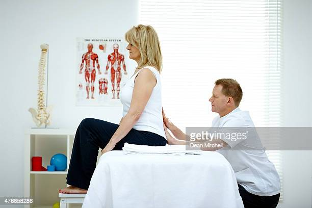Osteopath treating female patient with back problem