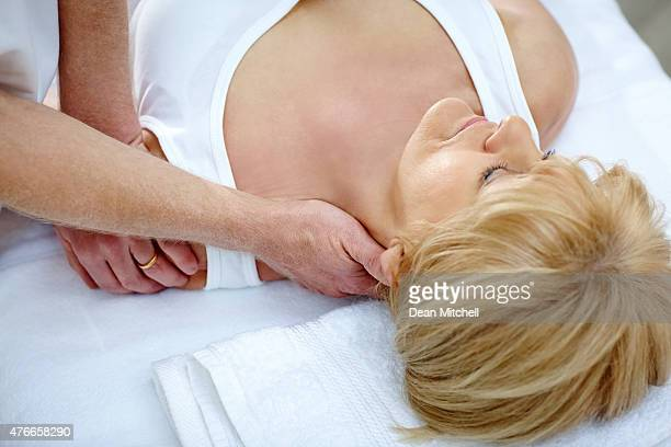 Osteopath treating female patient with neck problem