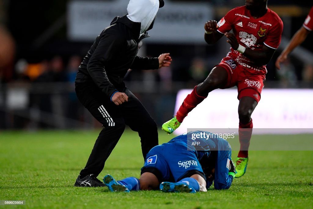 Ostersund's goalkeeper Aly Keita (C) remains on the ground after a masked soccer spectator (L) attacked him during a football match between Jonkoping Sodra and Ostersund in Jonkoping on August 15, 2016. / AFP PHOTO / TT NEWS AGENCY / Mikael Fritzon / Sweden OUT