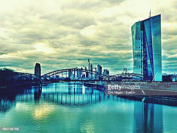 osthafenbrucke over river against cloudy sky in city - european central bank stock photos and pictures