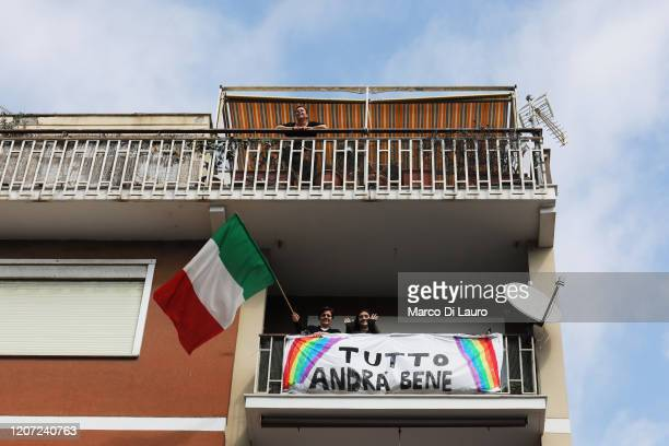 "Ostia residents display a banner which reads ""everything will be fine"" while look out the windows during a musical flash mob to shown their gratitude..."
