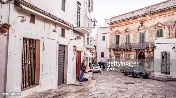 ミュージシャンとオスチュニ通りは通行人にギターを弾きます。オストゥニは、イタリアのプリャ州ブリンディジ州の海岸から約8キロに位置する都市とコムネです。 - ブリンディシ ストックフォトと画像