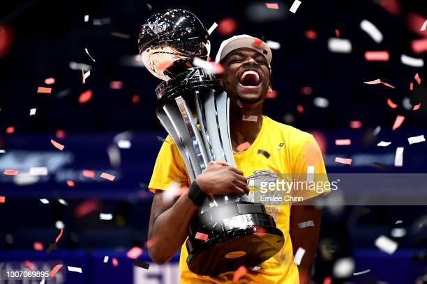Osun Osunniyi of the St. Bonaventure Bonnies celebrates with the championship trophy following their 74-65 win over the Virginia Commonwealth Rams in...