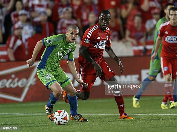 Osvaldo Alonso of Seattle Sounders FC tries to break away from JeVaughn Watson of FC Dallas at Toyota Stadium on April 12 2014 in Frisco Texas