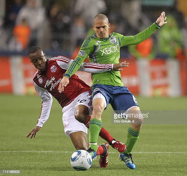 Osvaldo Alonso of the Seattle Sounders FC battles Rodney Wallace of the Portland Timbers at Qwest Field on May 14 2011 in Seattle Washington The...