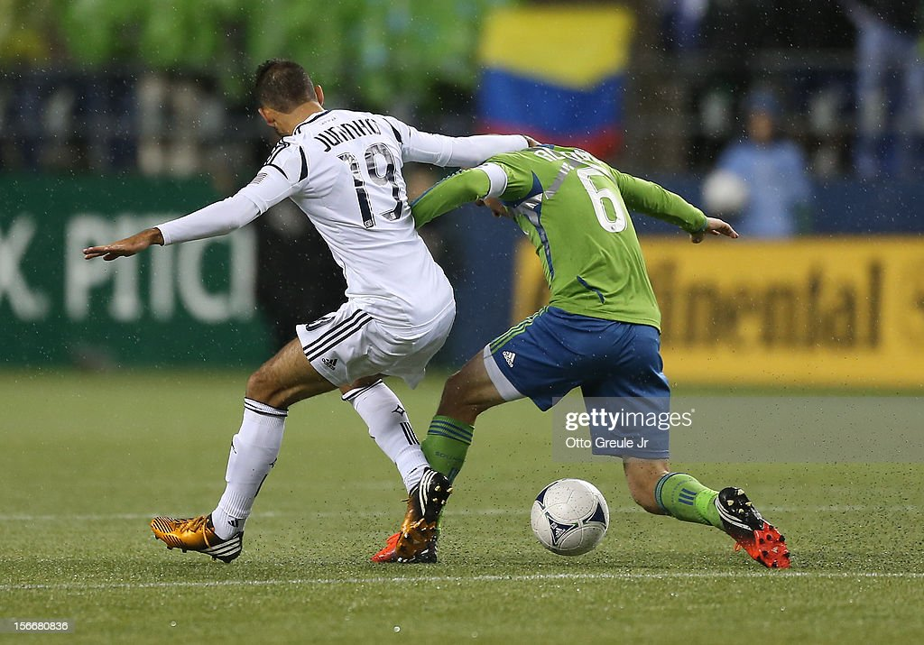 Osvaldo Alonso #6 of the Seattle Sounders FC dribbles against Juninho #19 of the Los Angeles Galaxy during Leg 2 of the Western Conference Championship at CenturyLink Field on November 18, 2012 in Seattle, Washington. Alonso was issued a yellow card on the play, and the Galaxy defeated the Sounders 2-1, winning the aggregate playoff 4-2.