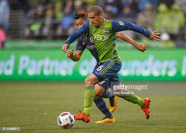 Osvaldo Alonso of the Seattle Sounders FC dribbles against Roger Espinoza of Sporting Kansas City at CenturyLink Field on March 6 2016 in Seattle...