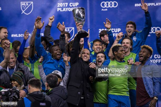 Osvaldo Alonso of the Seattle Sounders hoists the championship trophy as other members of of the Seattle Sounders celebrate after the second leg of...