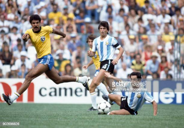 Osvaldo Ardiles of Argentina slides in to take the ball from Toninho Cerezo of Brazil during the FIFA World Cup match between Argentina and Brazil at...