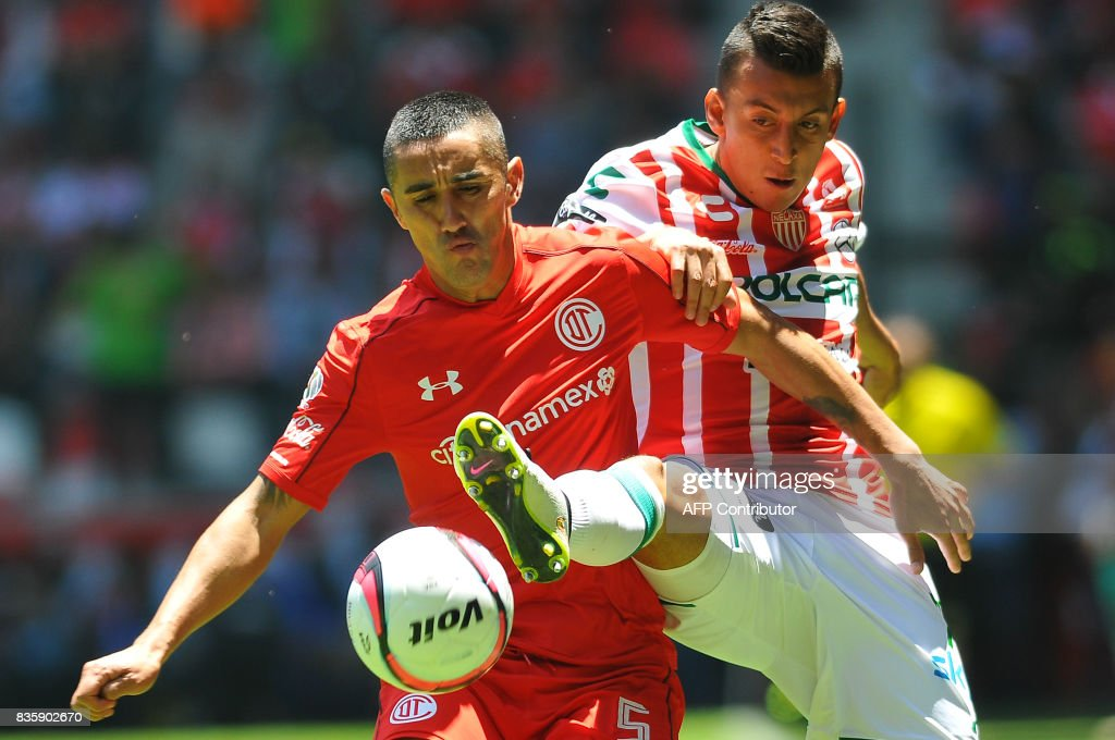 Osvaldo Gonzalez (L) of Toluca vies for the ball with Daniel Alvarez of Necaxa during their Mexican Apertura football tournament match at the Nemesio Diez stadium in Toluca, Mexico, on August 20, 2017. /