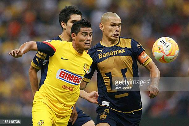 Osvaldo Martinez of America struggles for the ball with Dario Veron of Pumas during a match between America and Pumas as part of the Clausura 2013...