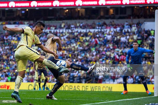 Osvaldo Martinez of America tries to score against Dar'io Ver—on of Pumas during the 17th round match between America and Pumas UNAM as part of the...