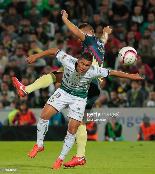 Osvaldo Martinez of Santos fights for the ball with Miguel Samudio of America during the 17th round match between Santos Laguna and America as part...