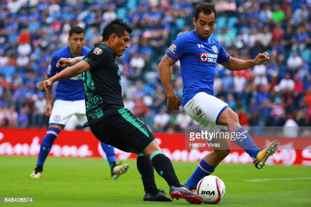 Osvaldo Martinez of Santos Laguna struggles for the ball with Adrian Aldrete of Cruz Azul during the 9th round match between Cruz Azul and Santos...