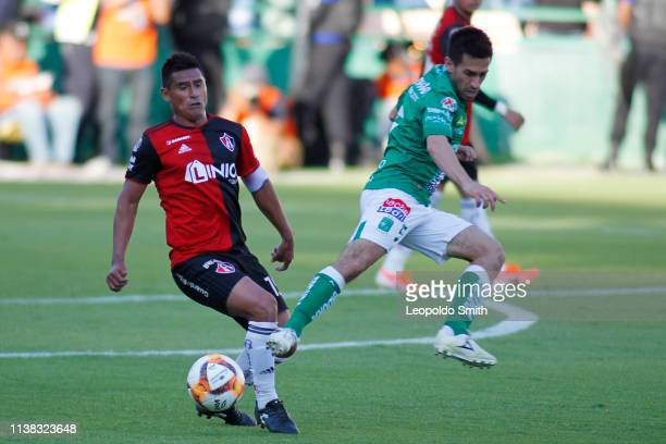 Osvaldo Martínez of Atlas struggles for the ball with Fernando Navarro of Leon during the 15th round match between Leon and Atlas as part of the...