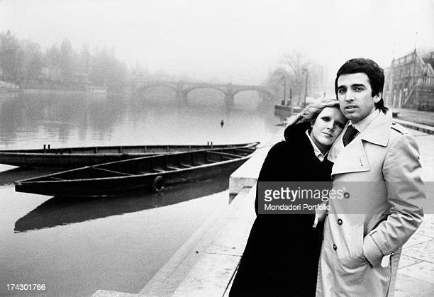 Osvaldo Paterlini hugs Italian singer Orietta Berti on his bosom in a dull day nearby two boats can be seen on a river Turin 1974