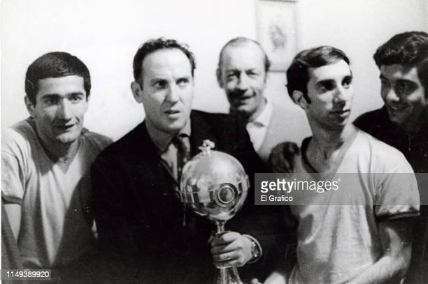 Osvaldo Zubeldía coach of Estudiantes poses with the trophy of the Libertadores Cup 1968 next to his players Juan Ramon Veron and Carlos Bilardo on...