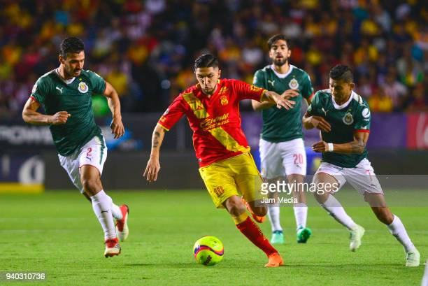 Oswaldo Alanis and Rodolfo Pizarro of Chivas defend against Diego Valdes of Morelia during the 13th round match between Morelia and Chivas as part of...