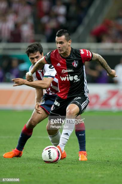 Oswaldo Alanis of Chivas fights for the ball with Milton Caraglio ofAtlas during the 16th round match between Chivas and Atlas as part of the Torneo...