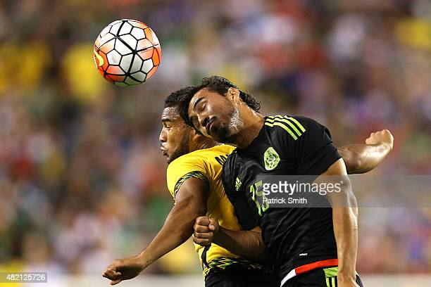 Oswaldo Alanis of Mexico and Jobi McAnuff of Jamaica battle for a head ball in the first half during the CONCACAF Gold Cup Final at Lincoln Financial...