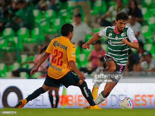 Oswaldo Alanis of Santos dribbles Armando Zamorano during a match between Santos Laguna and Morelia as part of 12th round Apertura 2014 Liga MX at...