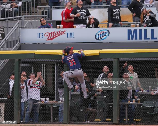 Oswaldo Arcia of the Minnesota Twins and fans watch as a home run ball hit by Alejandro De Aza of the Chicago White Sox sails out of the park during...