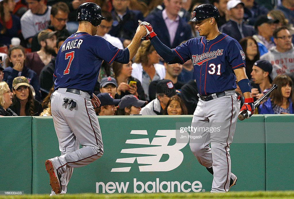 Oswaldo Arcia #31 of the Minnesota Twins congratulates Joe Mauer #7 after scoring in the 5th inning against the Boston Red Sox at Fenway Park on May 8, 2013 in Boston, Massachusetts.