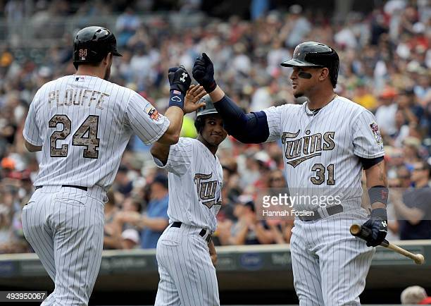 Oswaldo Arcia of the Minnesota Twins congratulates teammate Trevor Plouffe on a solo home run against the Texas Rangers during the first inning of...