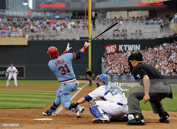 Oswaldo Arcia of the Minnesota Twins hits a grand slam as catcher Jonathan Lucroy of the Milwaukee Brewers looks on during the third inning of the...
