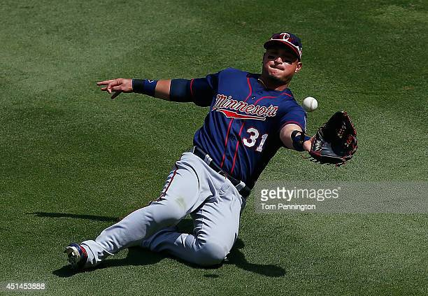 Oswaldo Arcia of the Minnesota Twins makes a sliding catch for the out on a fly ball hit by Adrian Beltre of the Texas Rangers in the bottom of the...