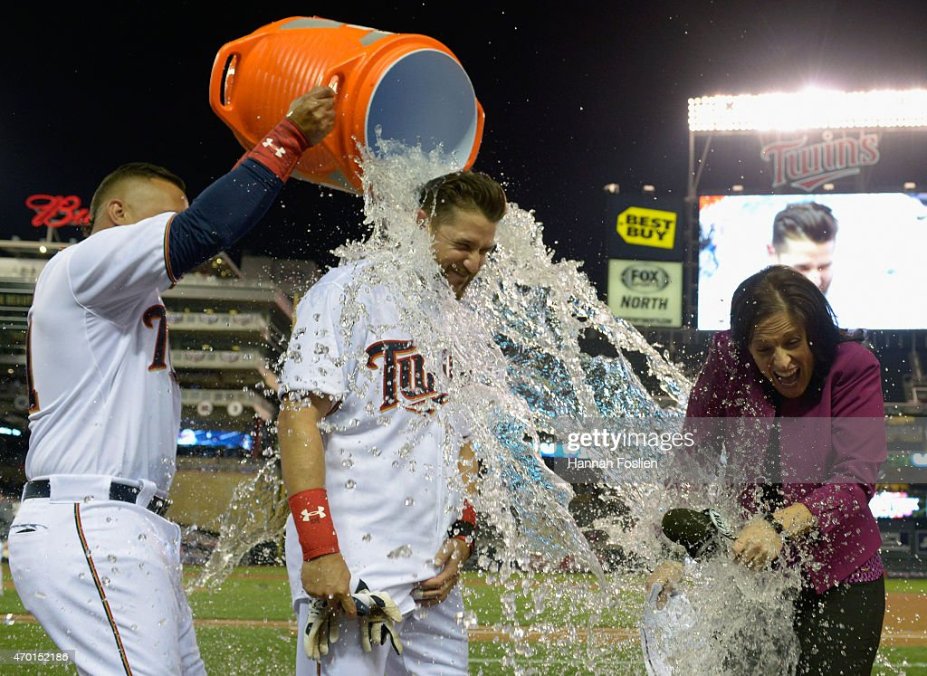 Oswaldo Arcia #31 of the Minnesota Twins pours ice water on teammate Trevor Plouffe #24 and tv reporter Marney Gellner after Plouffe hit a walk-off solo home run against the Cleveland Indians in the eleventh inning of the game on April 17, 2015 at Target Field in Minneapolis, Minnesota. The Twins defeated the Indians 3-2 in eleven innings.