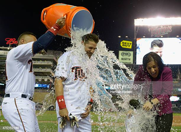 Oswaldo Arcia of the Minnesota Twins pours ice water on teammate Trevor Plouffe and tv reporter Marney Gellner after Plouffe hit a walkoff solo home...