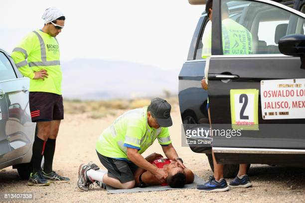 Oswaldo Lopez receives first aid from a member of his support team Ernest Velarde during the STYR Labs Badwater 135 on July 11 2017 in Death Valley...