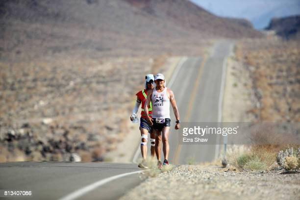 Oswaldo Lopez walks with a member of his support team Carlos Vasquez during the STYR Labs Badwater 135 on July 11 2017 in Death Valley California...