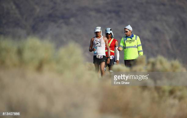 Oswaldo Lopez walks with members of his support team Carlos Vasquez and Ulises Sanchez during the STYR Labs Badwater 135 on July 11 2017 in Death...