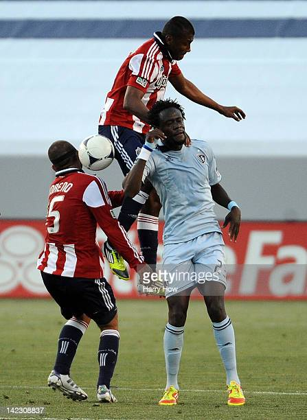 Oswaldo Minda and Alejandro Moreno of the Chivas USA get tangled with Kei Kamara of the Sporting KC for a ball during the first half at The Home...