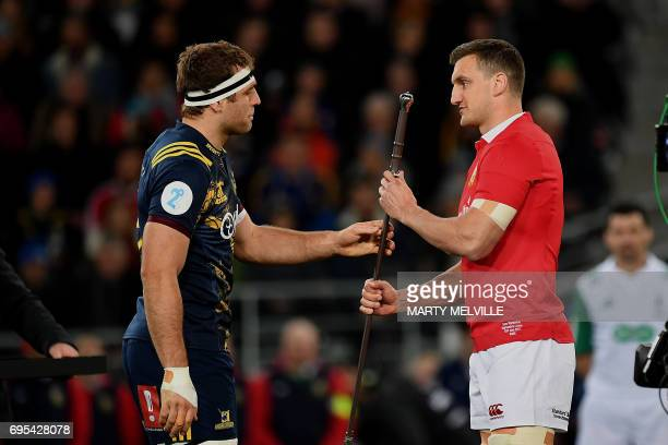 Otago Highlanders' captain Luke Whitelock presents British and Irish Lions' captain Sam Warburton with a Claymore sword during their rugby union...