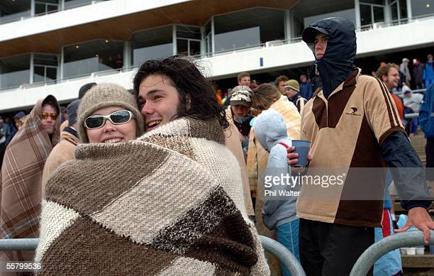 Otago students Andrea Luke and Nick O'Leary dress and cuddle against the winter conditions on the terraces at Carisbrook Stadium Dunedin New Zealand...