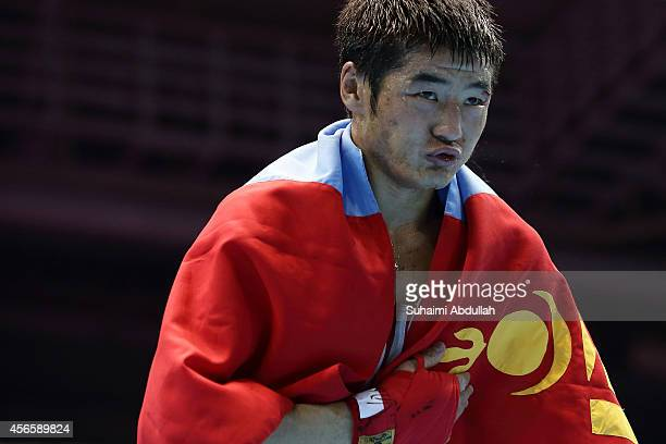 Otgondalai Dorjnyambuu of Mongolia drapes himself with the country flag after his win over Charly Suarez of Philippines during the men's boxing...