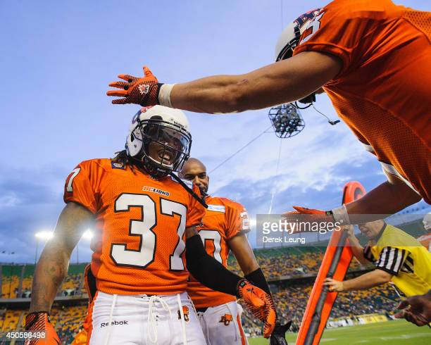 Otha Foster of the BC Lions gets congratulated by a teammate after a play against the Edmonton Eskimos during a CFL game at Commonwealth Stadium on...