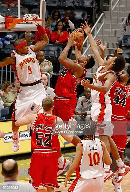 Othella Harrington of the Chicago Bulls grabs a rebound against Josh Childress and Josh Smith of the Atlanta Hawks during a game on January 24 2005...