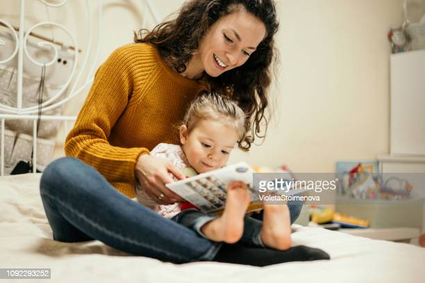 мother and daughter reading fairy tales - super mom stock photos and pictures