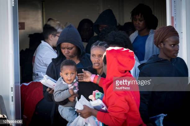 A other carries her child to take a bus to a center on January 9 Malaga Southern Spain