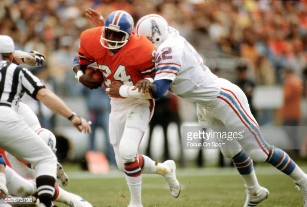 Otis Armstrong of the Denver Broncos gets tackled by Robert Brazile of the Houston Oilers during an NFL football game November 2 1980 at Mile High...