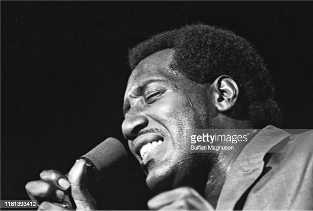 Otis Redding on stage in a light colored double breasted suit mike in right hand profile spotlight above