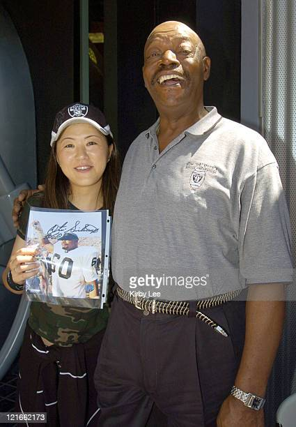 Otis Sistrunk a 1974 Pro Bowl defensive lineman and member of the Oakland Raiders Super XI championship team poses with female fan outside The Raider...