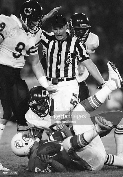 Otis Wilson of the Chicago Bears sacks Dan Marino of the Miami Dolphins as Dan Hampton looks on during the game at the Orange Bowl on December 2 1985...