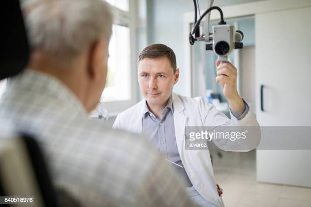 Otolaryngologist checking man's throat in his clinic