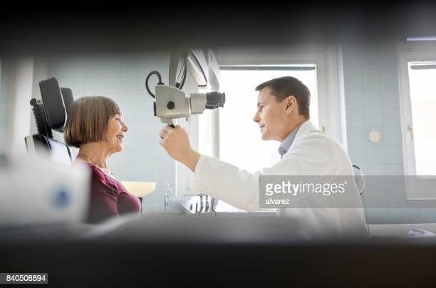 Otolaryngologist checking sore throat of senior patient